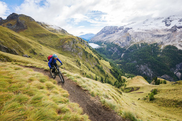 Young woman mountain biking in the Dolomite mountains, val gardena, south tyrol, italy