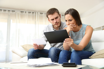 Worried couple checking bank account online