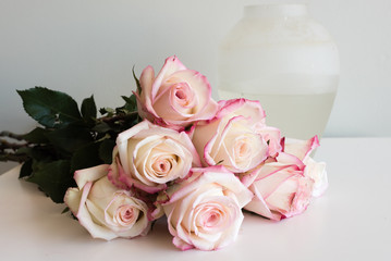 Close up of pink and cream roses on table next to glass vase (selective focus)