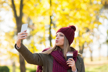 Young woman with takeaway coffee taking a selfie on smart phone in park in autumn