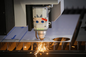 Laser cutting of flat sheet metal steel material with sparks.