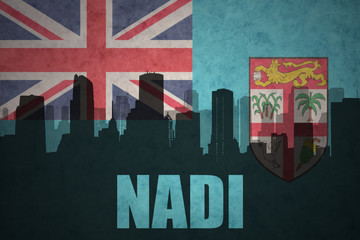 abstract silhouette of the city with text Nadi at the vintage Fiji flag