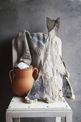 Salted cod fish and a rustic clay pot with sea salt  on a white