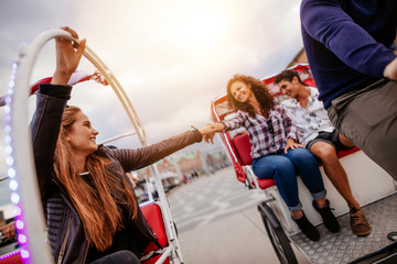 Teenage friends having fun on tricycles