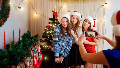 Friends make the photo on the phone on Christmas Day. Four beaut