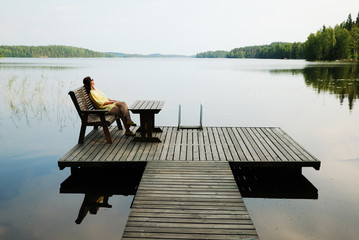 Lake with wooden platform and woman resting.