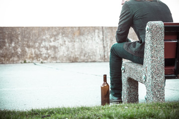 Man depressed with wine bottle sitting on bench outdoor