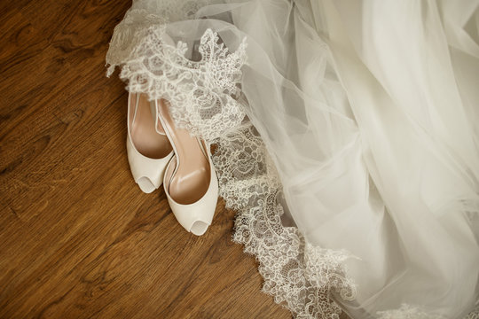Wedding accessories. Bridal shoes, white dress and veil on the wooden floor at wedding morning preparation, best for wedding banners, backgrounds, backdrops and wedding invitations