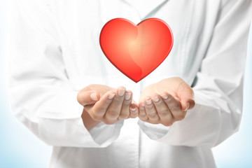 Cardiologist hands with red heart, closeup. Cardiology concept.
