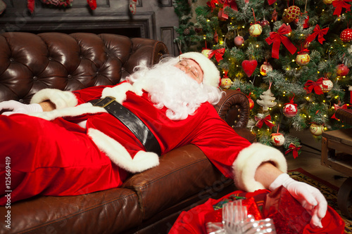 Santa Clause Snoozing In A Decorated Living Room With Sack Full Of Gifts By His Side Stock