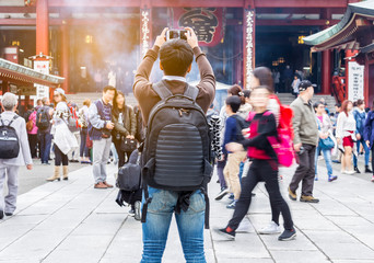 Asain tourist taking a photo of Asakusa temple by smart phone in Tokyo,Japan