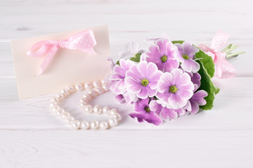 Bouquet of violet primroses with paper greeting card and pearl necklace