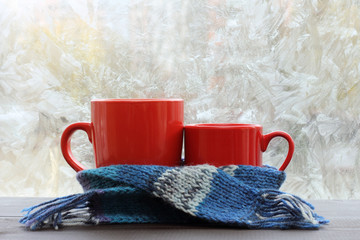 warming cozy atmosphere for breakfast/ big and small red circle standing together in a blue scarf on the background of a frosty window