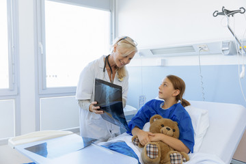 Pediatrician showing xray to patient Child In Hospital