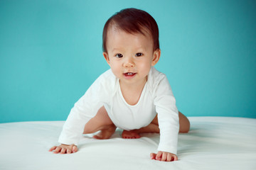 A crawling baby in diaper with blue background (soft focus on th