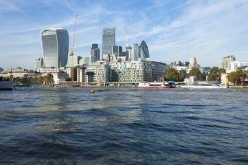 London skyline of the financial City center with the dark flowing waters of the River Thames