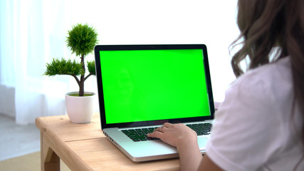 Asian girl using laptop with green screen
