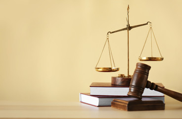 Justice scales, judge's gavel and books on wooden table and beige background