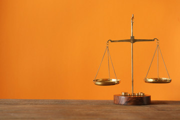 Justice scales on wooden table and  orange background