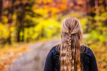 Young girl with beautiful hairs looking at wonderful nature in colorful autumn forest. Original wallpaper with space for your montage.