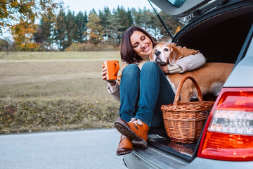 Woman with her dog have a tea time during their autumn auto trav
