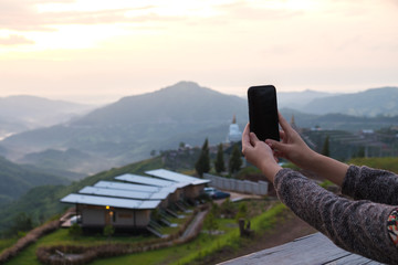 Young woman take photo of mountain view by smart phone in morning.