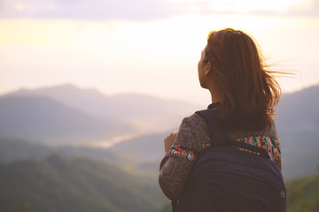 Hipster young woman with backpack enjoying sunrise view on mountain