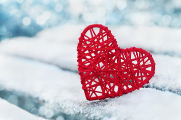 Red heart in snow with bokeh background. Valentines day card. Love winter.