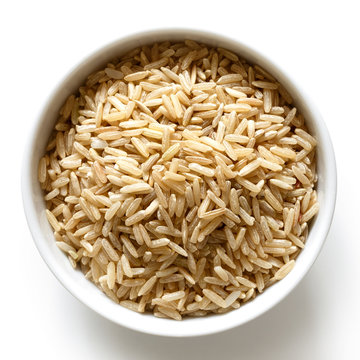 Bowl of long grain brown rice isolated on white from above.