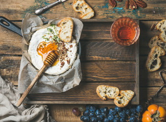 Homemade camembert cheese with honey and herbs in small pan, black grapes, persimmon, baguette slices, pecan nuts and glass of rose wine over rustic wooden background, top view, copy space