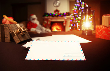 Letter to Santa Claus near the gift and candles.