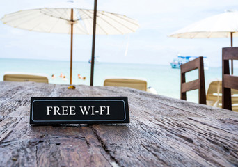 Free Wi-Fi banner on restaurant table, beach background