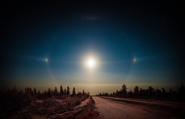 Winter landscape with road, moon and halo