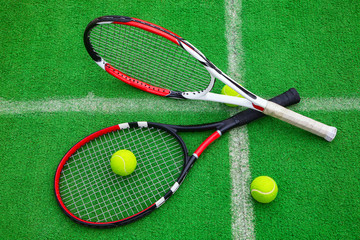 tennis racket with balls on green grass