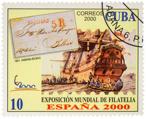 Ancient sailing ship and boats with sailors on postage stamp