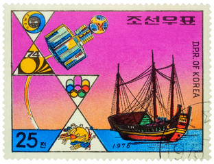 Ancient sailing ship and modern satellite on postage stamp