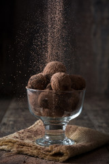 Throwing cocoa in a truffles on wooden background