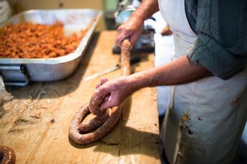 Man making sausages the traditional way using sausage filler.