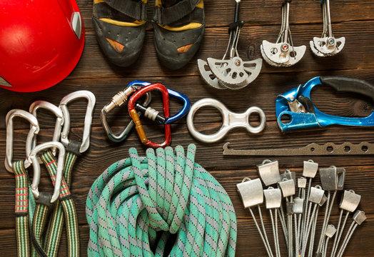 climbing and travel equipment on dark wooden background, top vie