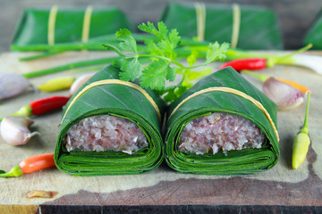 Sour pork, Thai northeastern style food which mixed pork rice garlic sugar and salt in banana leaf package