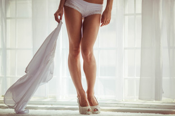 beautiful and athletic legs of the bride in wedding shoes