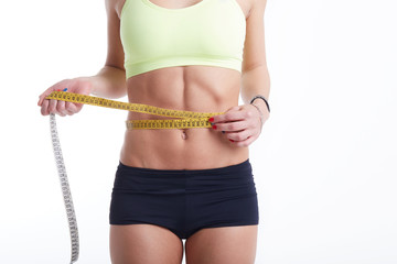 fit female measuring her waist