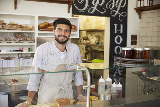 Small business owner behind the counter of a sandwich bar