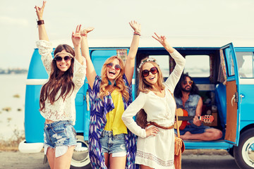happy hippie friends having fun over minivan car
