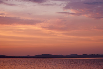 Russia. Khakassia. Sunrise on the Lake Shire. On the horizon, the silhouette of hills and mountains.