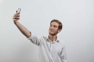 Young Adult Man in White Shirt Takes a Selfie with His Phone