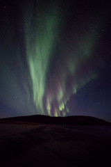 Gentle auroras explode from mountain near Tromso