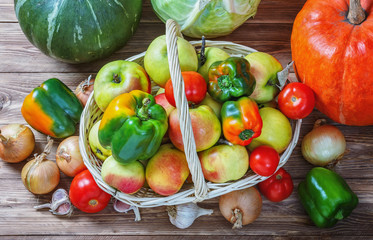 Apples, onions, garlic, tomatoes, cabbage and pumpkins on a wooden table.