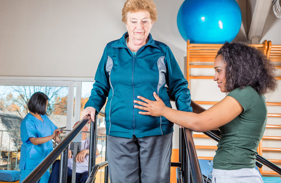 Senior citizens working out at a gym helped by multi race traine