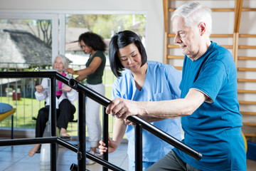 Senior citizens working out at gym with multi racial trainers he